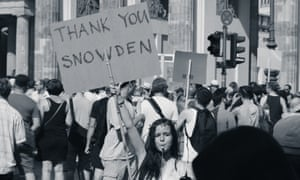 A woman holds a placard that says THANK YOU SNOWDEN.