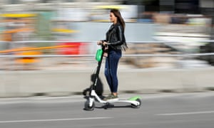 A woman rides an electric Lime scooter.