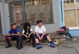 A group of friends sit on a shop stoop.