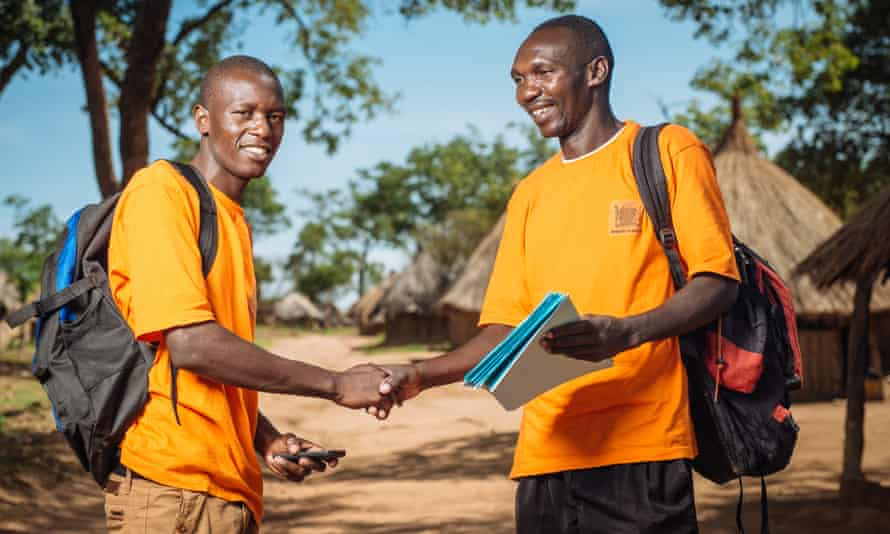 Ephraim Sikalundu, Data collector, and Vincent Munsaka, Community health worker shake hands standing in front of the grass huts of Harmony village