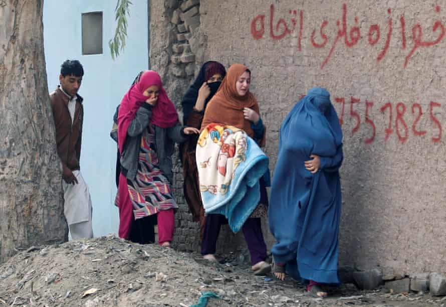 Afghan women leave the site of a blast and gun fire in Jalalabad, Afghanistan