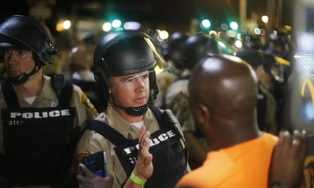 Police confront protesters in Ferguson, Missouri, a year after Michael Brown was killed.
