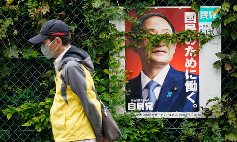 A man wearing a face mask walks past a poster of outgoing Japanese prime minister Yoshihide Suga