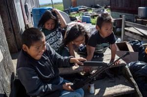 Village children shoot a pellet gun at soda cans.