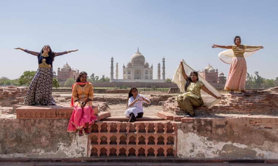 Five women who survived acid attacks standing in front of the Taj Mahal