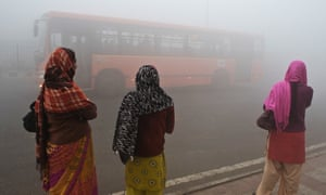 Women wait for a bus early on a polluted morning in Delhi.
