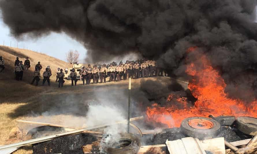 Tires burn as soldiers and law enforcement officers stand in formation to force Dakota Access pipeline protesters off private land.