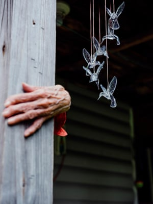 An elderly woman holds onto a post for support on the porch outside her home in Webster county, West Virginia.