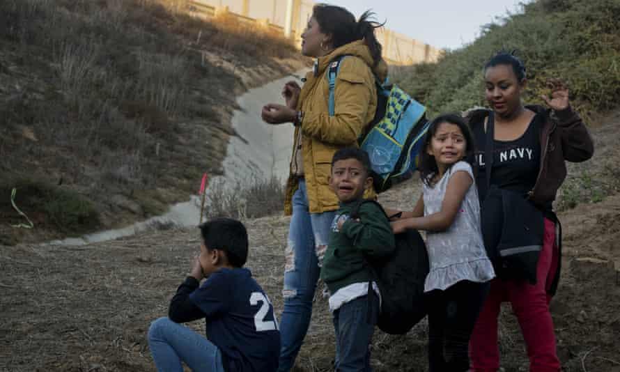 Honduran migrants react as they surrender to US border patrol on 2 December.