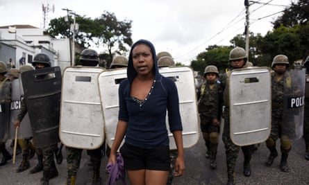 Military police stand guard next to supporters of opposition candidate Salvador Nasralla as they hold a protest march on Wednesday in Tegucigalpa.