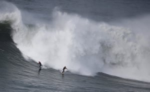 Surfers drop in on a large wave at Praia do Norte in Nazaré, Portugal.