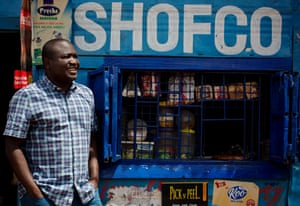 Kennedy Odede, entrepreneur and co founder of Shining Hope for Communities (SHOFCO), a non-profit organisation that tackles urban poverty and gender inequity, poses for a photograph outside a shop bearing his organisation's name in Kibera, Nairobi, Kenya.