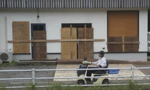 A man looks at a shop, protected by wood boards, as Typhoon Hagibis approaches in town of Kiho, Mie Prefecture.