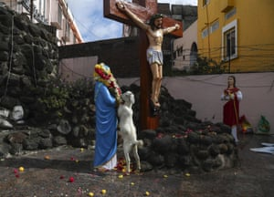 A goat feeds on a flower garland that was placed on a statue of Mother Mary in front of a crucifix at the shrine of Our Lady of Health during the annual feast of the birth of Virgin Mary in Hyderabad