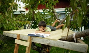 A boy reading a book in a treehouse.