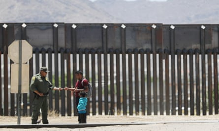 A US border patrol agent checks the identification of a migrant with a child on the US side of the border with Mexico in El Paso, Texas, on 18 May.