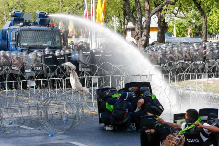 Riot police spray water cannon at protesters outside Government House in Bangkok.
