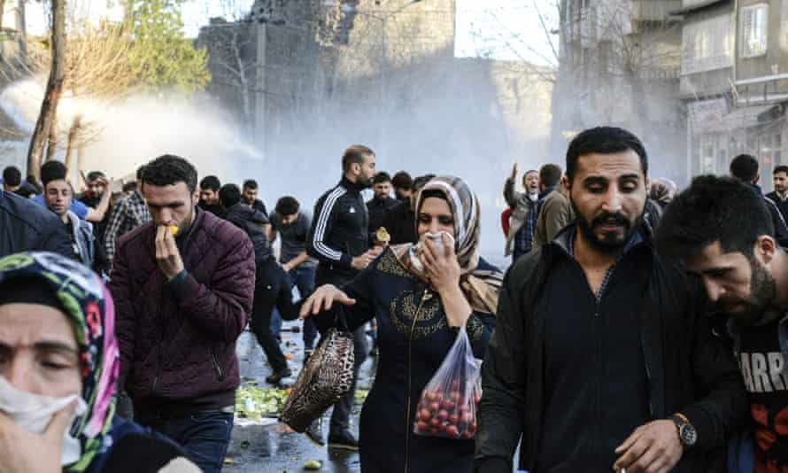 People run away from tear gas in the centre of Diyarbakir.