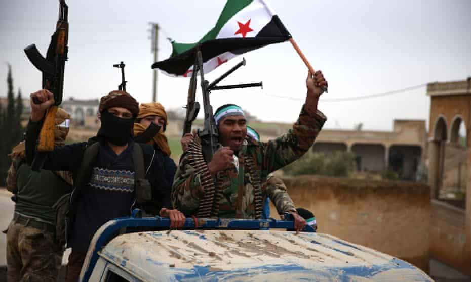 Turkish-backed Syrian fighters raise the opposition flag as they arrive in the border rebel-held town of Qirata after leaving their barracks in Jarabulus on their way to Manbij on 25 December.