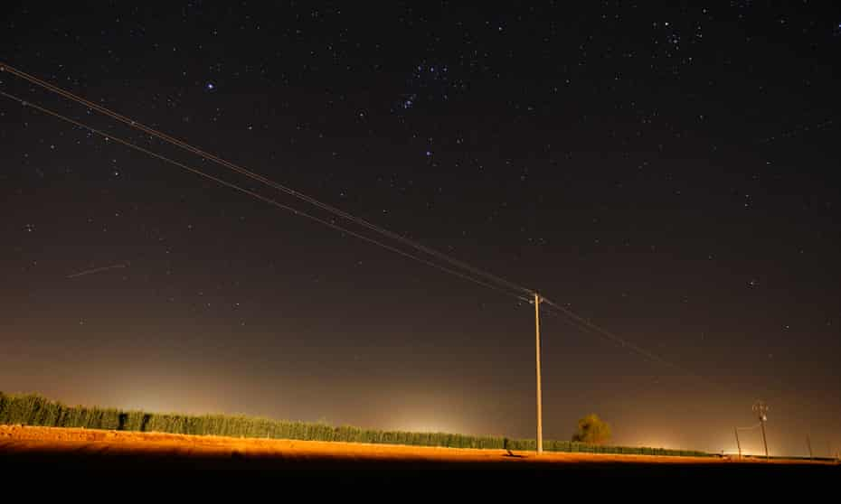 The gas flares of a fracking site illuminates a country road in California