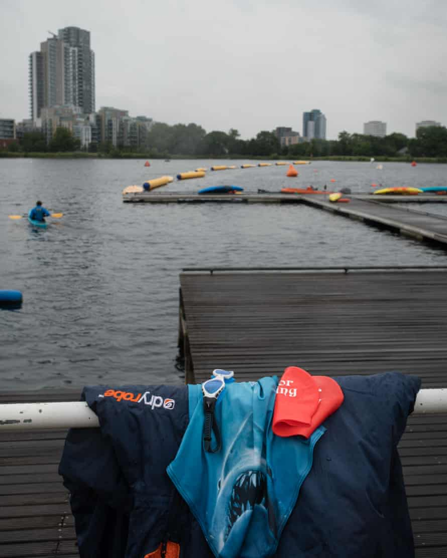 Swimming clothes at the edge of the reservoir with tall buildings in the distance