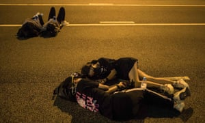 Protesters lie on a main road near the government headquarters in Hong Kong. Hong Kong police criticised an 'illegal' blockade of its headquarters.