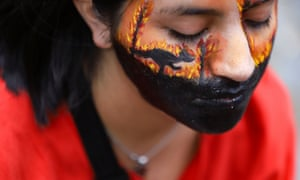 A demonstrator wearing face paint attends a protest over the bushfires crisis, outside the Australian embassy in Buenos Aires