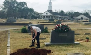 A man rakes soil over a grave in the Lee family cemetery plot on Saturday.