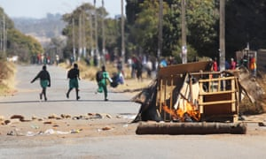Schoolchildren run past a burning barricade in Harare