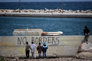 Children play at the coast near the open refugee camp of Souda, Greece