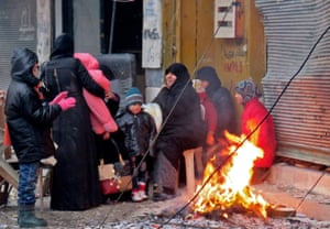 Syrians keep warm next to a fire as they arrive in Aleppo's Fardos neighbourhood