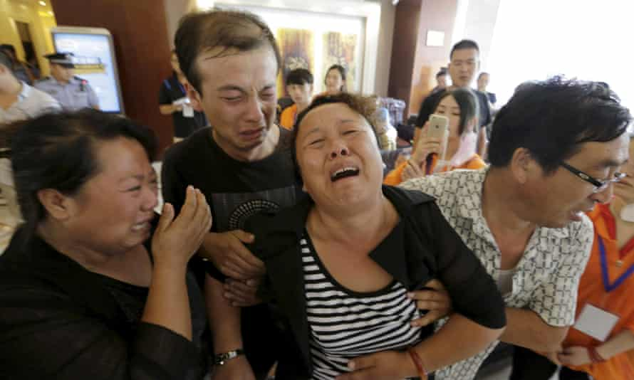 The mother of a missing firefighter weeps outside a press conference in Tiajin