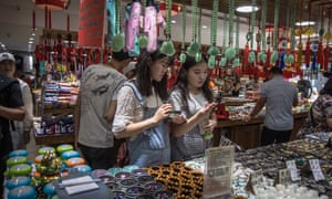 Chinese people visit a shop at the Wangfujing shopping district in Beijing, China