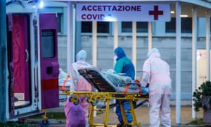 A patient on a stretcher is transported by medical workers wearing protective suits at the Columbus hospital unit of the Gemelli hospital in Rome.