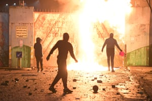 Fires burn as youths clash at the Peace Gate in Belfast.
