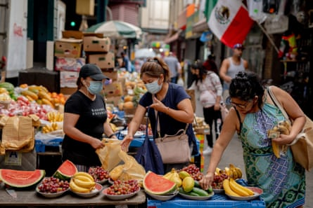 Customers shop for fruit at a street vendor in Corona neighborhood in the Queens borough of New York, U.S., on Saturday, June 27, 2020.