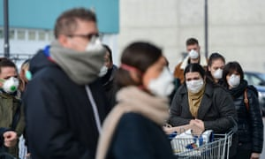 Residents wearing respiratory mask wait to be given access to shop in a supermarket in small groups of forty people in the  Casalpusterlengo.