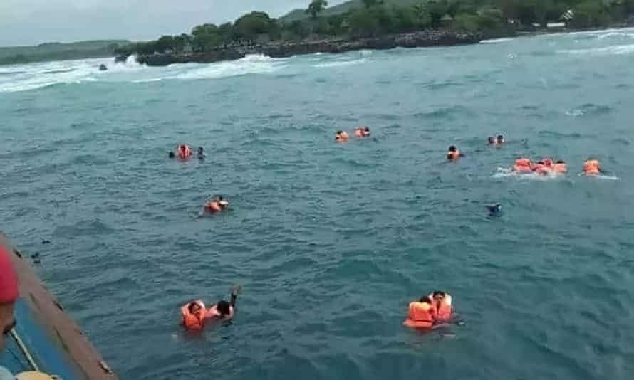 Passengers float in the sea awaiting help.