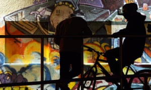 Two boys with bikes, hang around in front of a graffiti wall