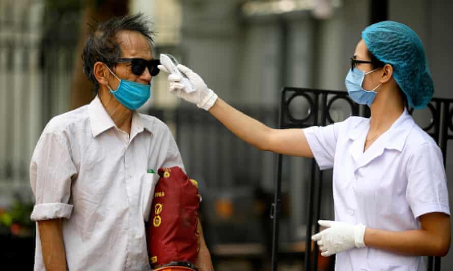 A man has his temperature checked in Hanoi, Vietnam.