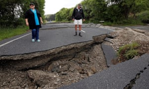 Residents Chris and Viv Young look at damage the earthquake caused to State Highway One near the town of Ward, south of Blenheim in New Zealand's South Island.