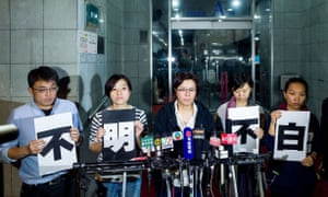 Ming Pao staff holding signs which say 'The truth is unclear' outside the Hong Kong newspaper's headquarters