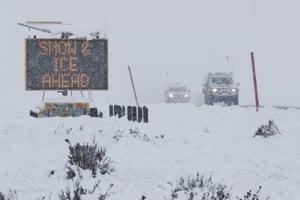 Cars drive through a blizzard on the Snowy Mountains Highway near Kiandra