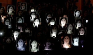 People hold up photos of anti-corruption journalist Daphne Caruana Galizia during a protest marking eighteen months since her assassination, outside the office of Prime Minister Muscat in Valletta
