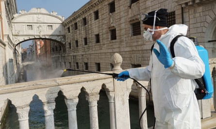 A worker disinfects the historical Marciana area of Venice in Italy.