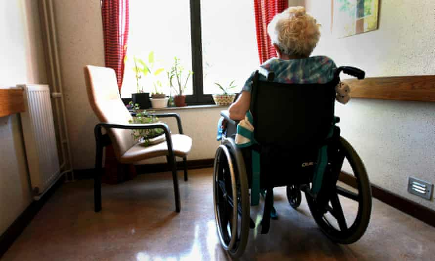 woman with grey hair in wheelchair in small room looking out window