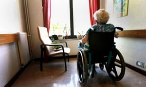 Old woman in aged care home looks out window.