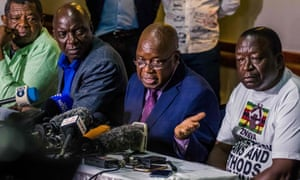 Christopher Mutsvangwa (centre) speaks during a press conference in Harare.