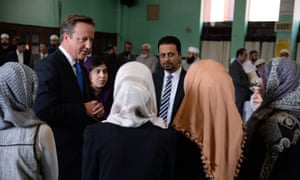David Cameron talking to young Muslim women at Jamia Masjid mosque in Manchester in 2013. Cameron has invited key Muslim figures to join a new community engagement forum.