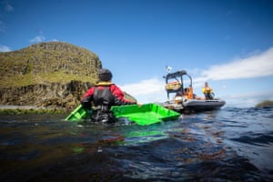 Crew from the Beluga II load plastic from Eilean Tighe beaches into a rigid-hulled inflatable boat (rhib) for disposal.